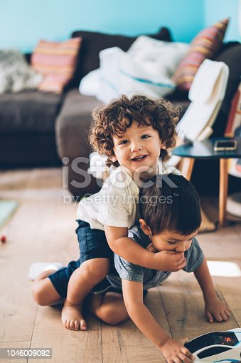 Two playful liitle boys - toddlers, playing on the floor
