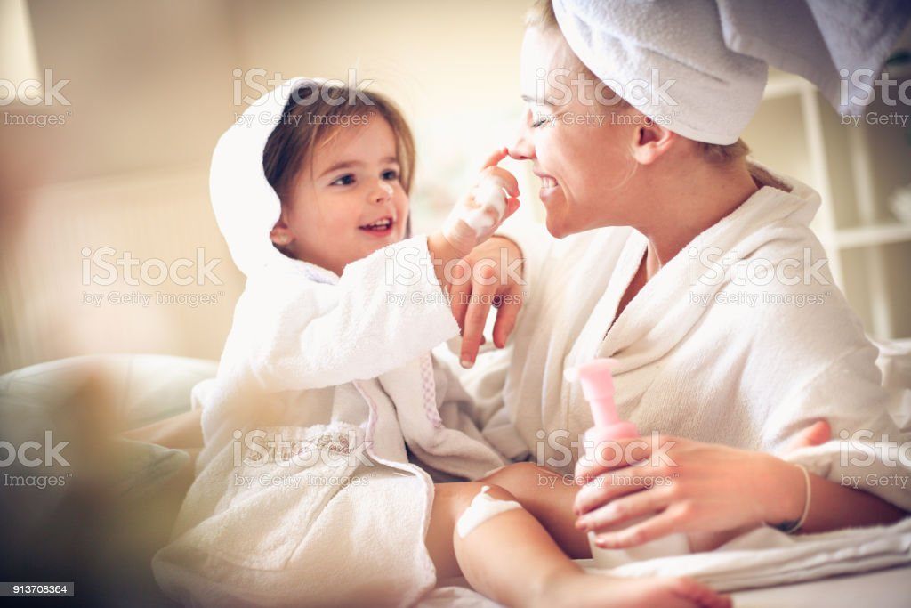 Playful with mommy after bath. Little girl. stock photo