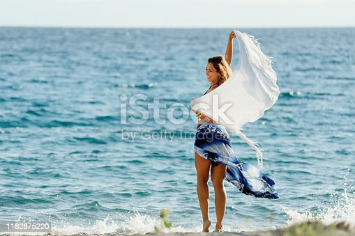 Young happy woman with a shawl having fun at the beach during summer vacation.