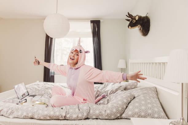playful woman in unicorn costume in bedroom - unicorn bed imagens e fotografias de stock