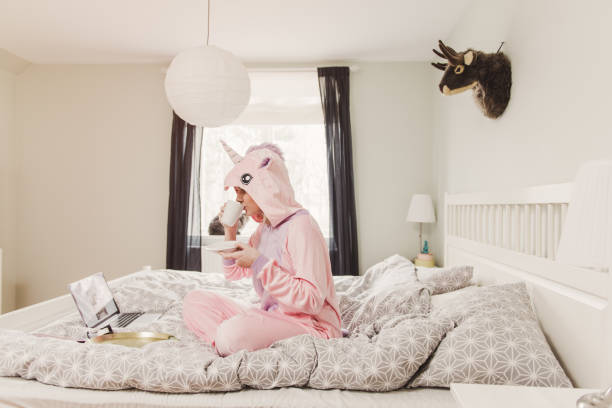 Playful woman in unicorn costume in bedroom stock photo