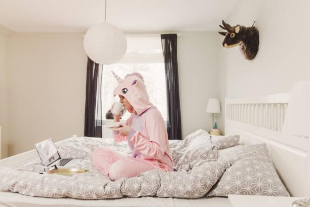 verspielte frau im einhorn kostüm im schlafzimmer - flippige outfits stock-fotos und bilder