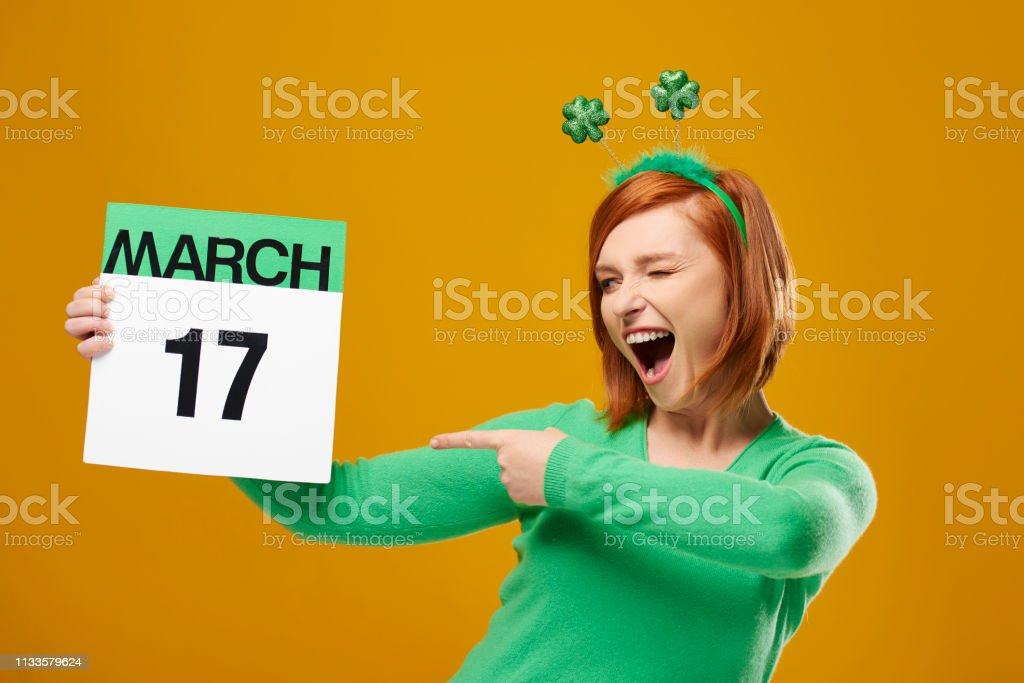 Playful woman pointing at Saint Patrick's Day calendar stock photo