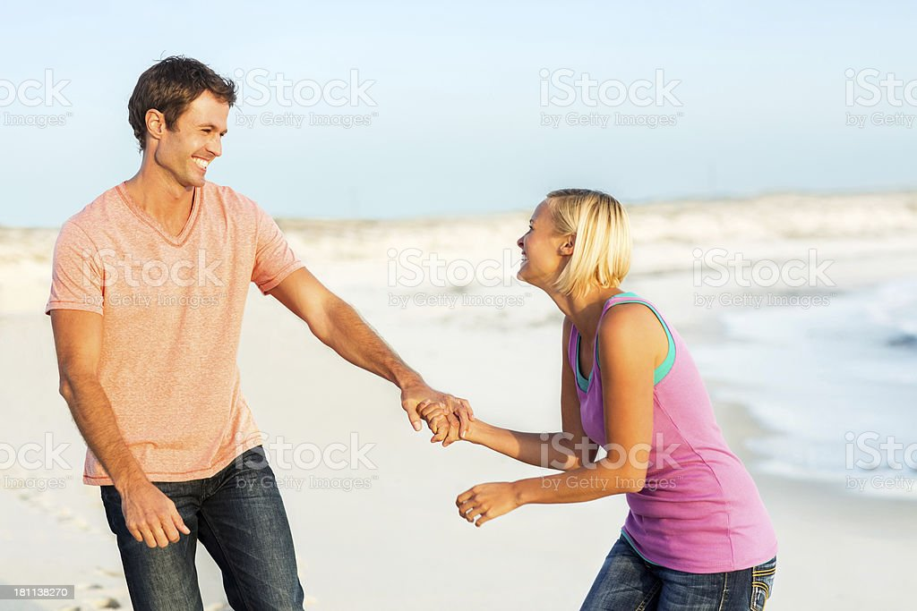 Playful Woman Pulling Man's Hand On Beach royalty-free stock photo