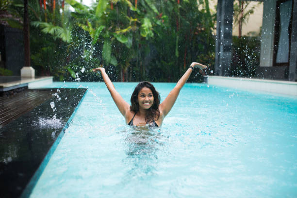 Playful woman splashing water in swimming pool stock photo