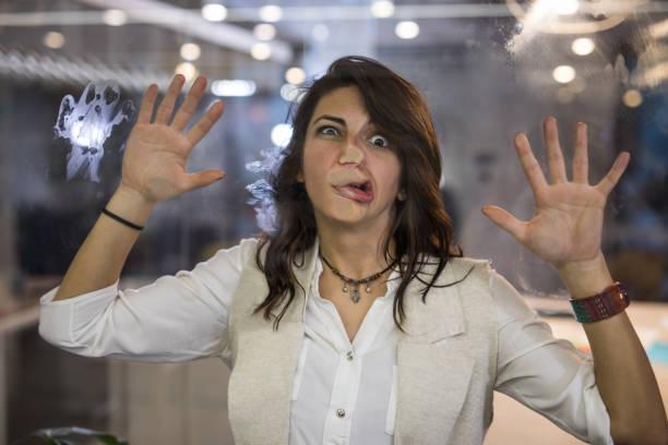 mulher lúdica com o rosto colado na parede de vidro, olhando para a câmera. - descrição geral - fotografias e filmes do acervo