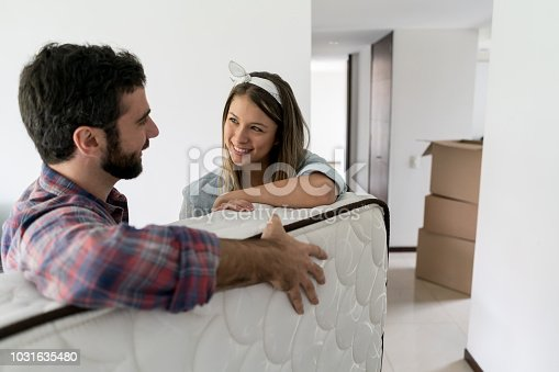 Playful woman with her partner while he is moving in a matress into their new place looking very happy and smiling