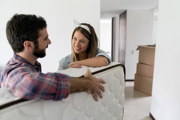 femme ludique avec son partenaire alors qu'il se déplace dans un matelas dans leur nouveau lieu - matelas photos et images de collection