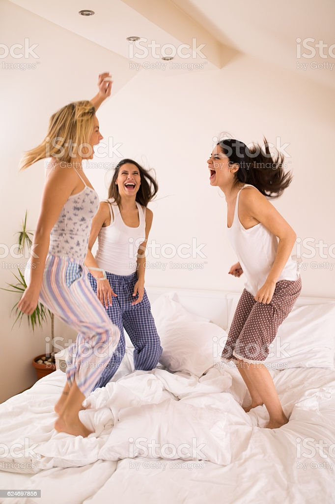 Playful women having fun at slumber party jumping on bed stock photo