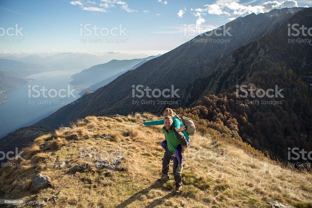 Playful young couple on mountain top, piggyback stock photo