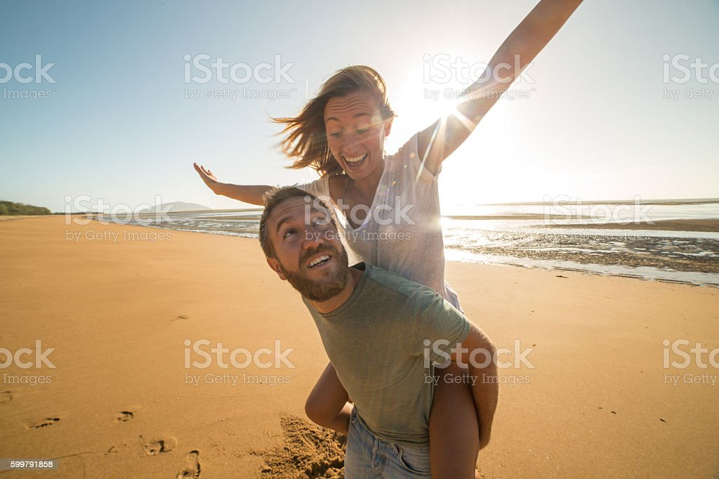 Playful young couple on the beach at sunset stock photo