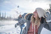Playful young couple throwing snowballs at each other at sunset having fun and enjoying winter vacations