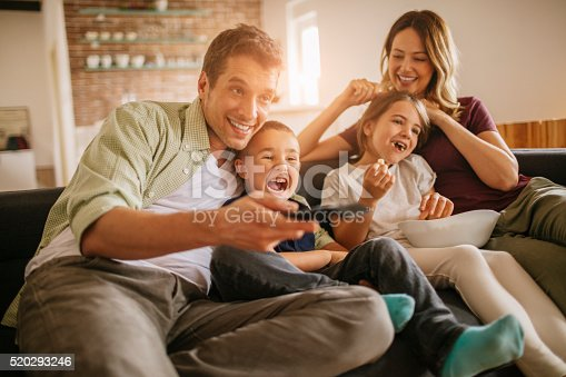 istock Playful young family watching television 520293246