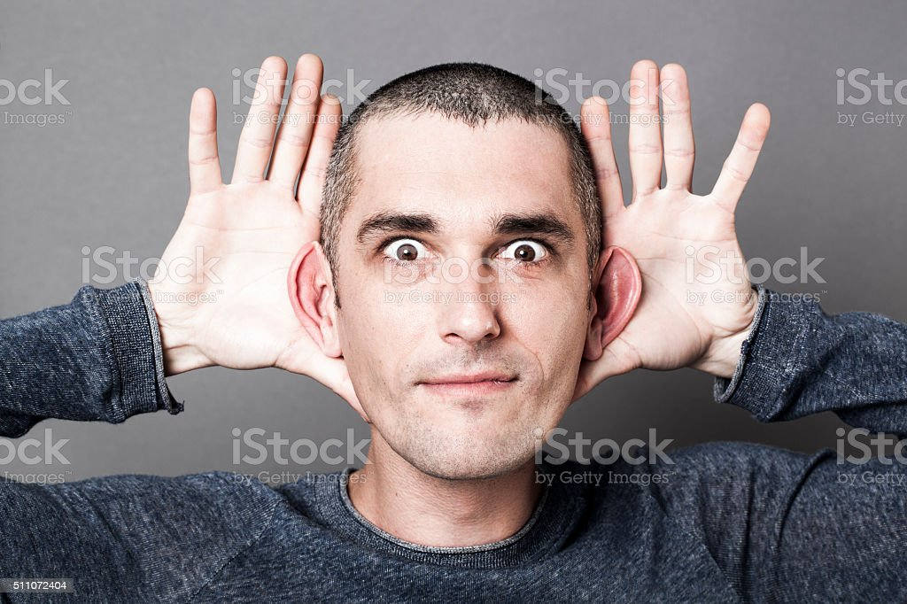 playful young man emphasizing the size of ears for curiosity stock photo