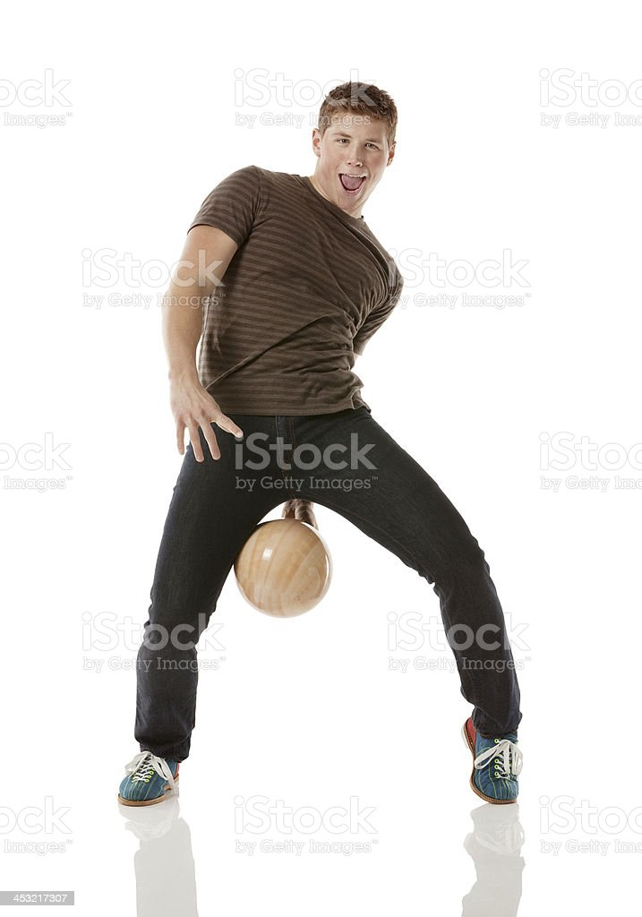 Playful young man with a bowling ball stock photo