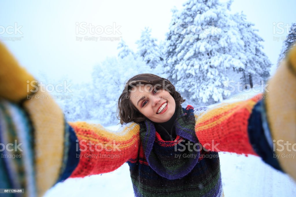 Playful young woman having fun in snow stock photo