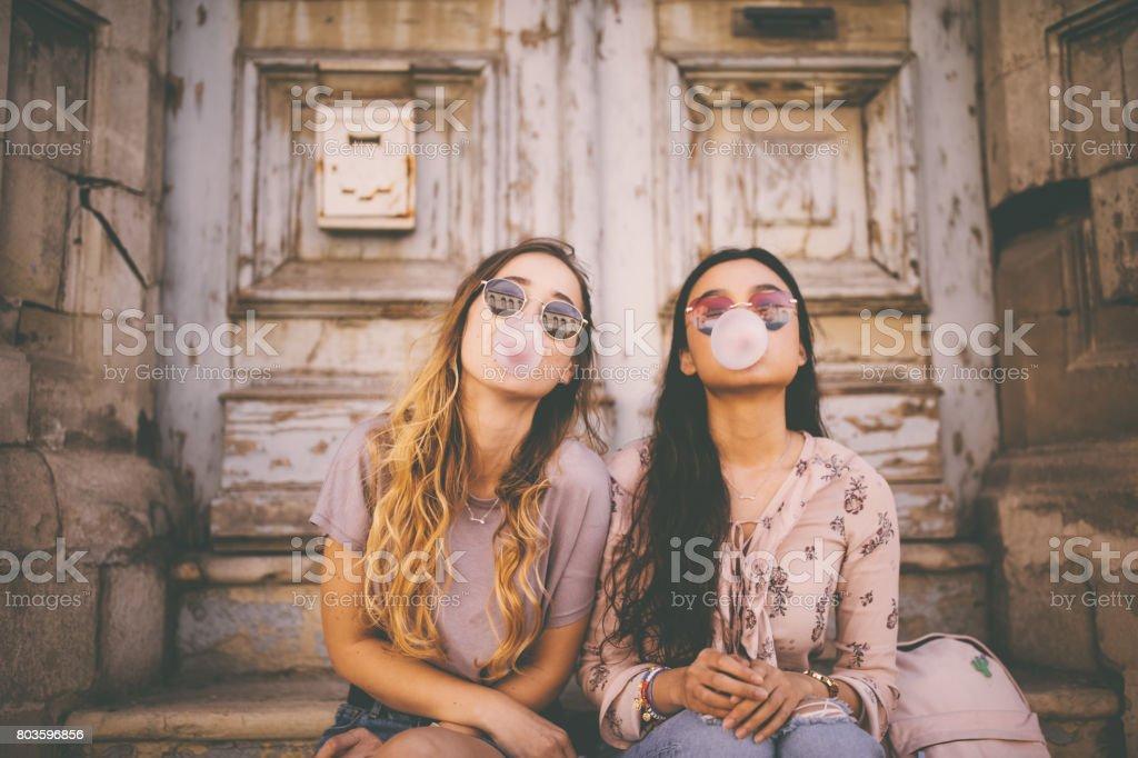 Mujeres jóvenes juguetones soplar chicles rosados en ciudad vieja - foto de stock