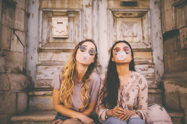 Playful young women blowing pink bubble gums in old city stock photo