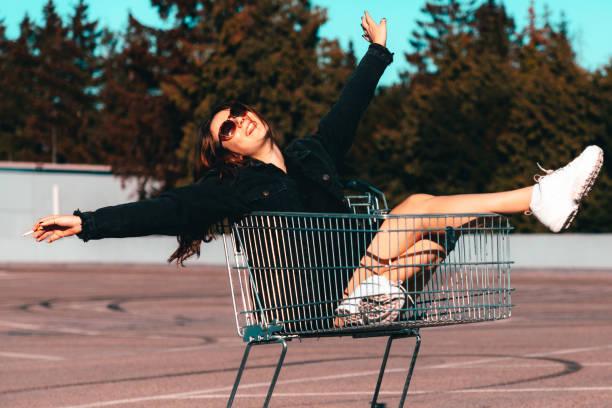 Playful young women having fun sitting in shopping cart stock photo