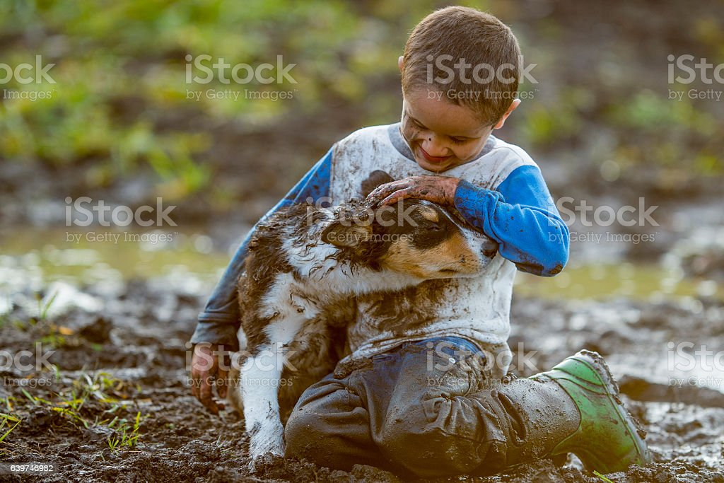 Playfully Making a Mess in the Mud stock photo