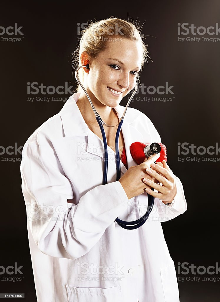 Playfully smiling woman doctor checks Valentine heart with stethoscope royalty-free stock photo