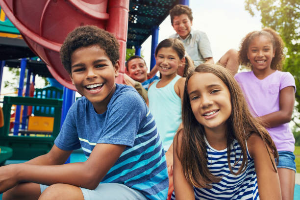 Playground and friends, fun guaranteed Shot of a group of young friends hanging out together at a playground pre adolescent child stock pictures, royalty-free photos & images