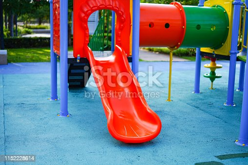 656743520istockphoto Playground for kid children having fun with colorful slide at yard activities in public park. 1152228614