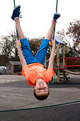 Boy hangs upside down from two ropes as he plays in an adventure playground  for children