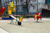 Moscow, Russia - April 26, 2020: Playground is closed due to coronavirus pandemic. A warning tape is block the swing. The children not play, they stay at home. Protection against disease covid-19