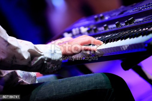Available light image of a keyboard player in live performance on stage at a music festival.  Close-up of right-hand fingers on keys.  Horizontal, copy space.  Some noise from medium ISO.