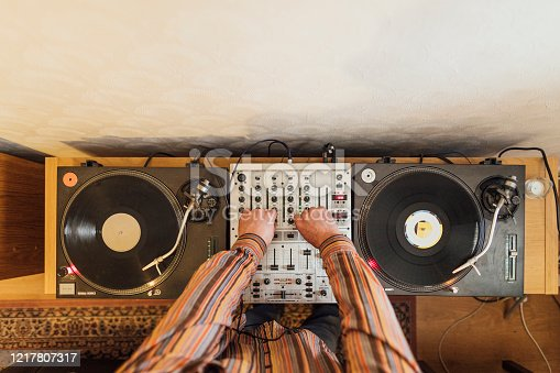 Directly above view of a Dj deck with an unrecognisable person mixing with it while at home.
