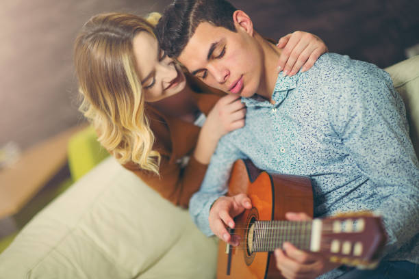 Playing a guitar Young and attractive couple sitting near the couch with a guitar. The male is playing the guitar. serenading stock pictures, royalty-free photos & images
