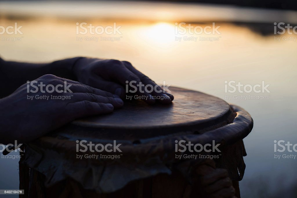 Playing a musical instrument jembe or atabaque stock photo