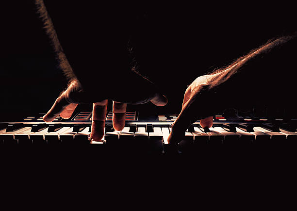 Playing a Piano or Synth Playing a keyboard, two male hands playing, accentuated contrasts. synthesizer stock pictures, royalty-free photos & images