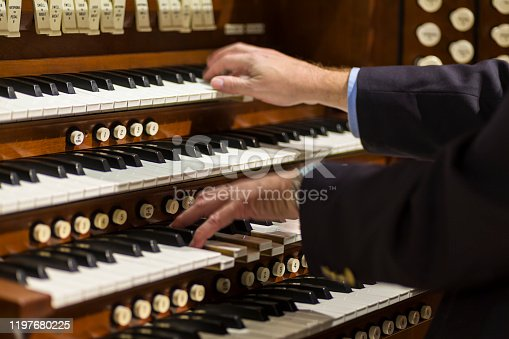 Close up view of a organist playing a church pipe organ with motion blur.