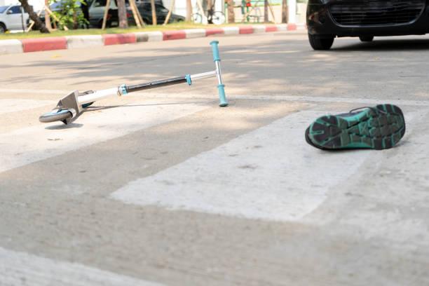 jugar un scooter y ser golpeado por un coche, mientras que el uso de un crosswalk. - foto de stock