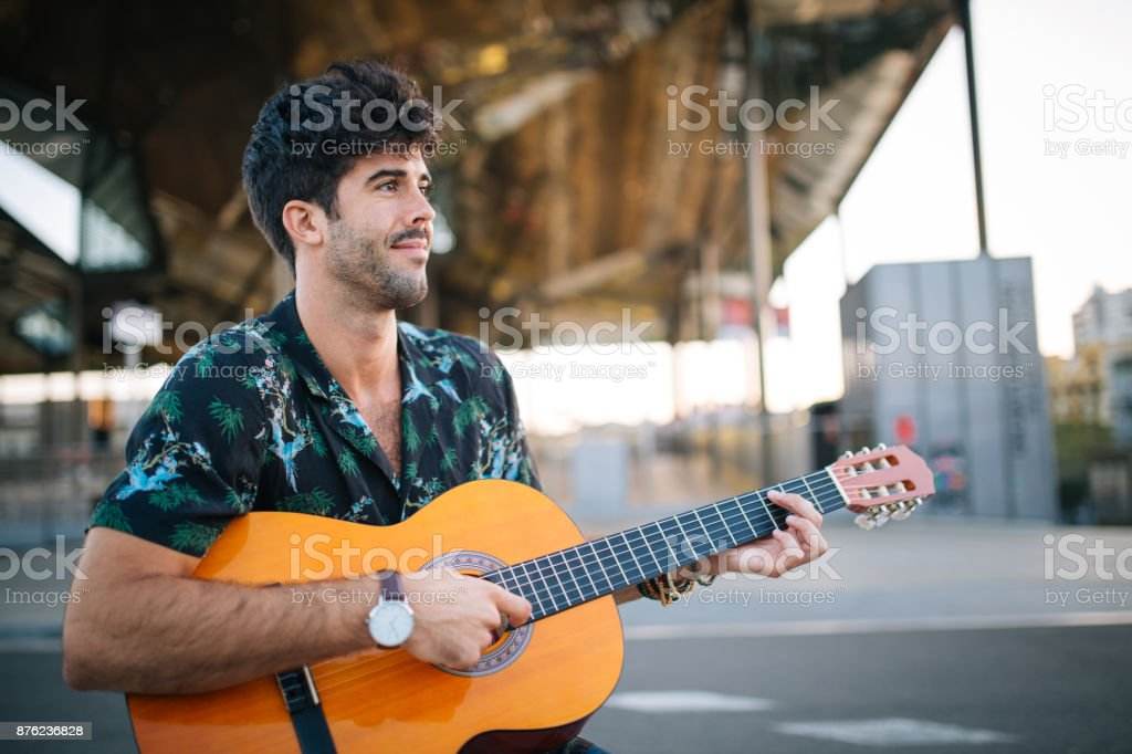 Playing acoustic guitar downtown stock photo