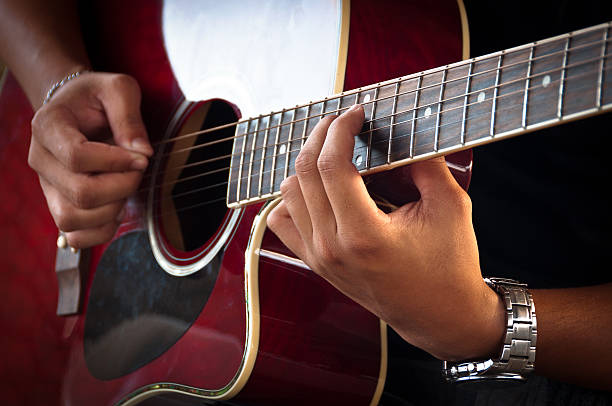 Playing Acoustic Guitar Hands of Young Man Playing Acoustic Guitar. serenading stock pictures, royalty-free photos & images