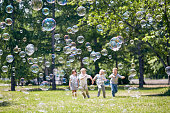 Green public park illuminated with sunbeams, colorful soap bubbles flying in air, group of little children playing active games