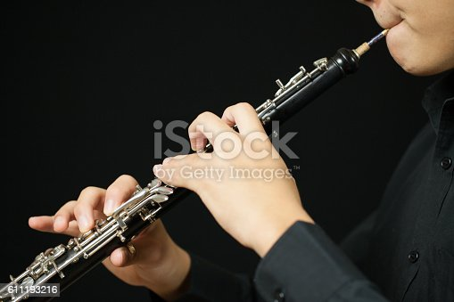 Close up of a person playing an oboe. Image shows the reed and the hand and finger positions. Studio shot on a black background.