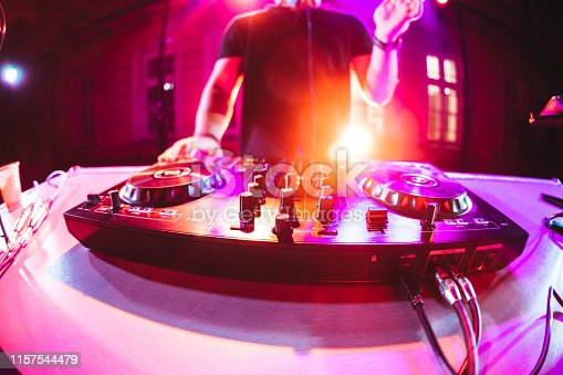Club, disco DJ playing and mixing music for crowd of happy people. Nightlife, concert lights, flares.