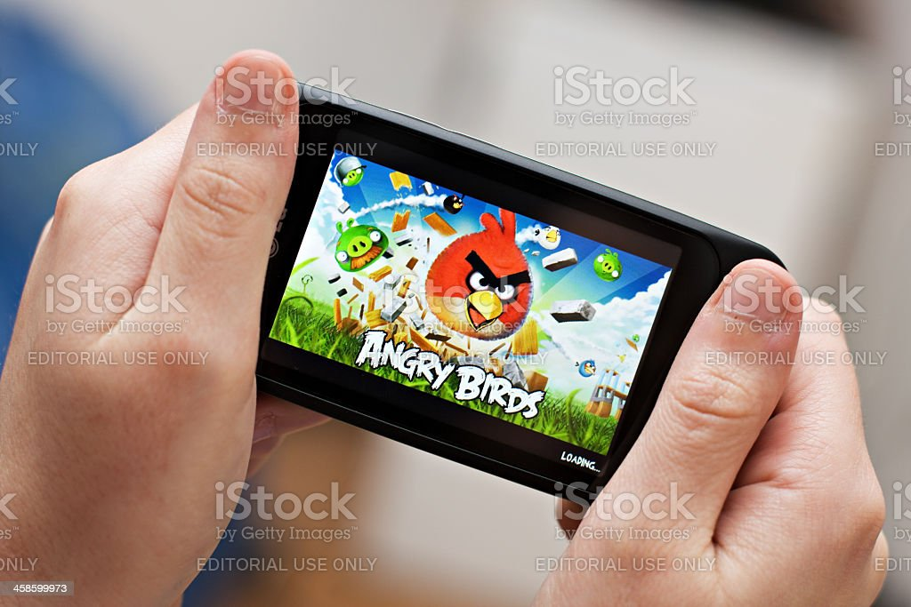 Playing Angry Birds on a smartphone royalty-free stock photo