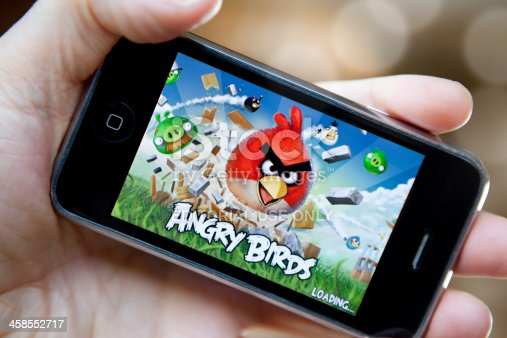 East Sussex, UK - March 25, 2011: Hand holding an Apple iPhone with screen showing the Angry Birds game app.