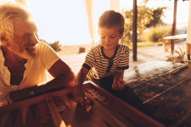 Playing backgammon with grandpa Photo of a little boy playing board games with his grandfather on a terrace of a family home at sunset backgammon stock pictures, royalty-free photos & images
