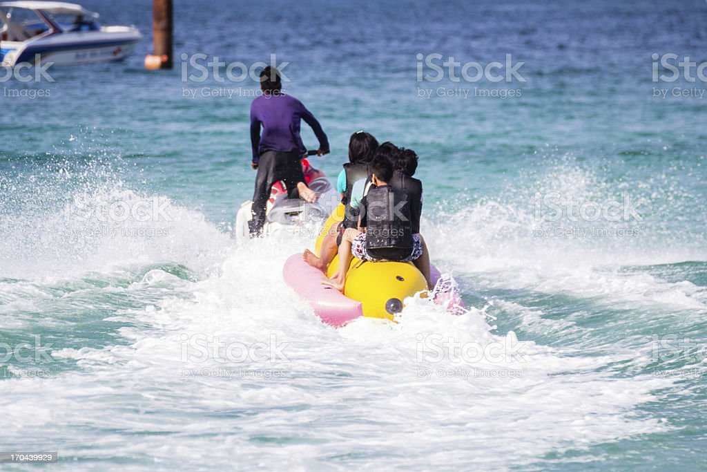 Playing banana boat in the sea stock photo
