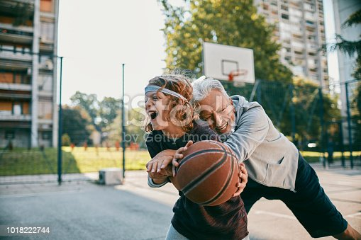 Close up of a grandfather playing basketball with his grandson