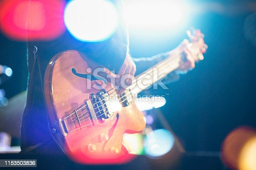 blurred bass guitar player on stage