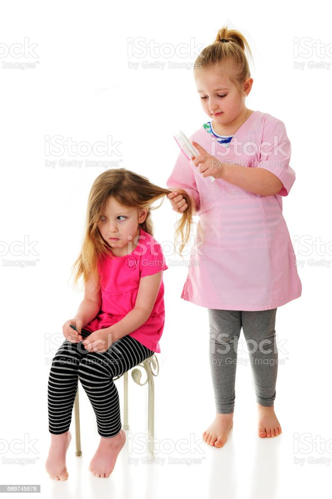 Playing Beautician on Sister's Hair stock photo