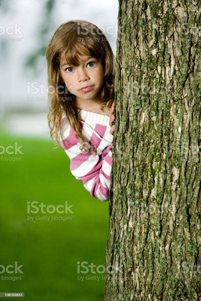 Playing behind the tree royalty-free stock photo