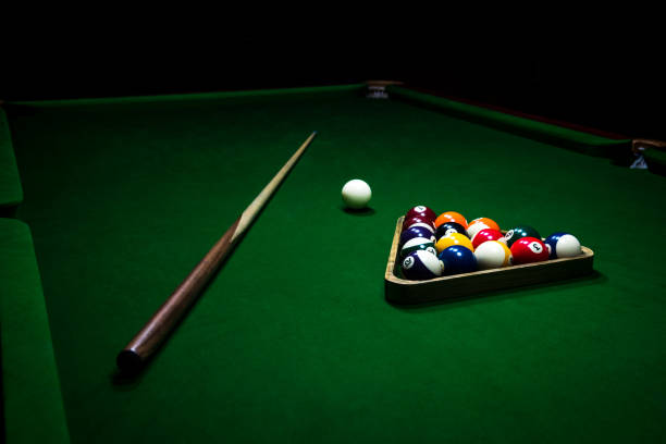 playing billiard. billiards balls and cue on green billiards table. - pool cue stock photos and pictures